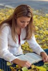girl reading Bible in yellow flowers